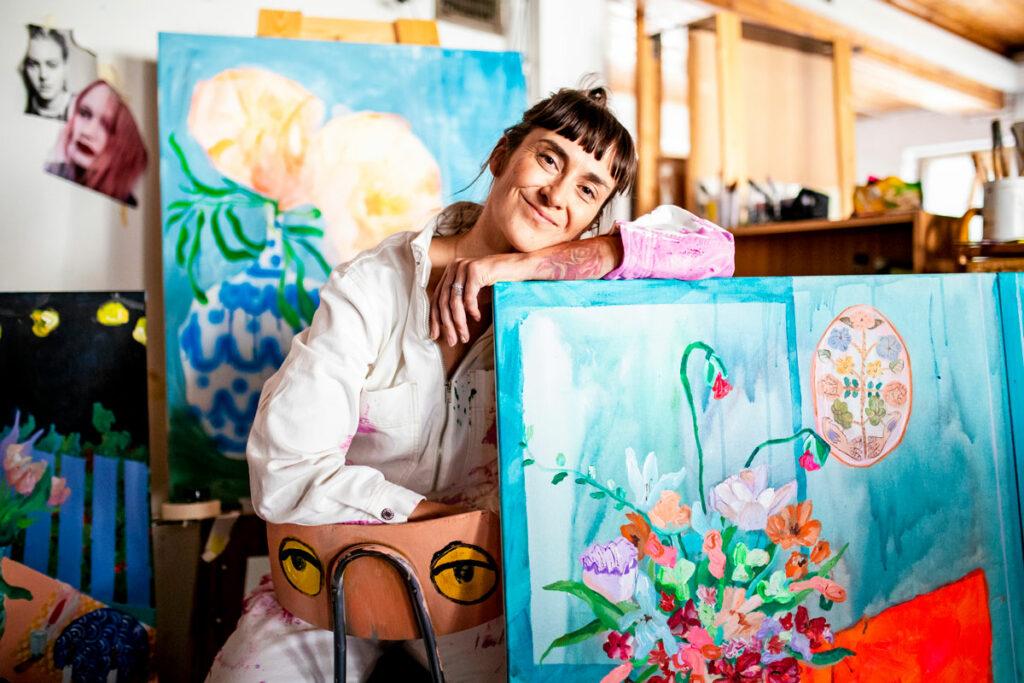 Laura Annala poseeraa taulunsa kanssa.
